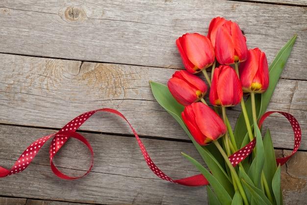 Свежие красные тюльпаны с лентой на деревянном фоне с копией пространства