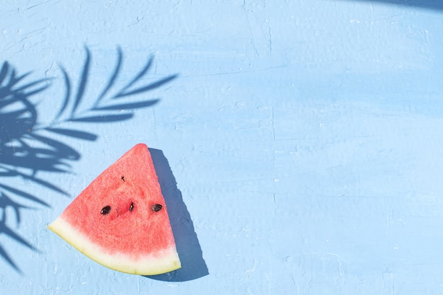 Fresh red watermelon slice isolated light blue background top view