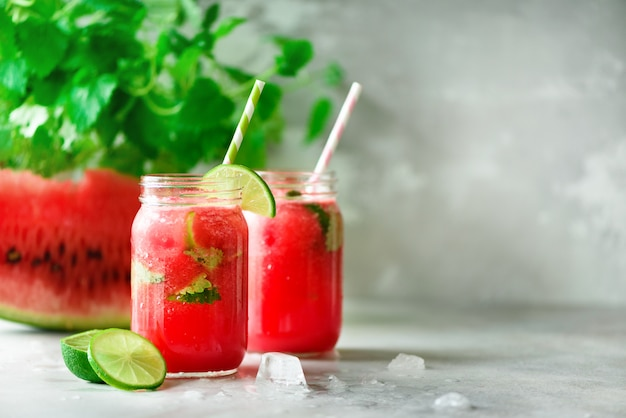 Fresh red watermelon slice and smoothie in glass jar with straw, ice, mint, lime