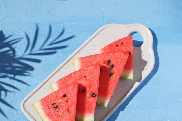 Fresh red watermelon slices isolated light blue background top view