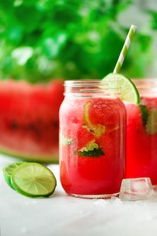 Fresh red watermelon smoothie in glass jar with straw, ice, mint and lime
