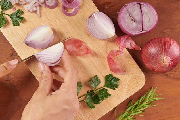 Fresh red whole and sliced onion. sliced red onion with parsley and rosemary . onion and slices on wooden cutting board. freshly picked from home growth organic garden. food concept.