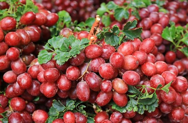地元の市場で新鮮な赤ワインのブドウの果実の背景