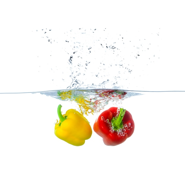 Fresh red and yellow paprika splashing in water