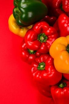 Свежий красный, желтый, зеленый болгарский перец на красном фоне.