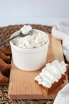 Fresh ricotta cheese in white ceramic bowl with rye sandwich on wooden cutting board