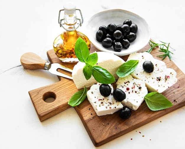 A fresh ricotta with basil leaves and olives  on wooden board, italian food concept