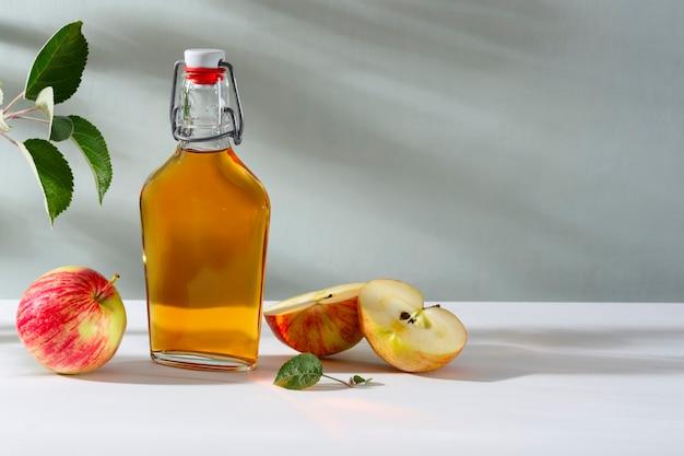 新鮮な熟したリンゴとリンゴ酢。ガラス瓶に入ったアップルサイダーと新鮮なリンゴ。明るい背景。