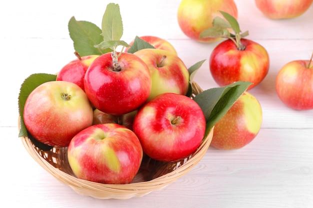 白い木製の背景にバスケットの新鮮な熟したリンゴ