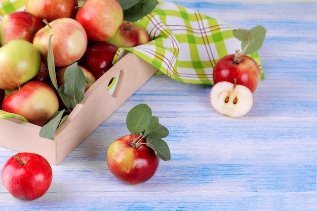 木製の背景に木製のトレイに新鮮な熟したリンゴ
