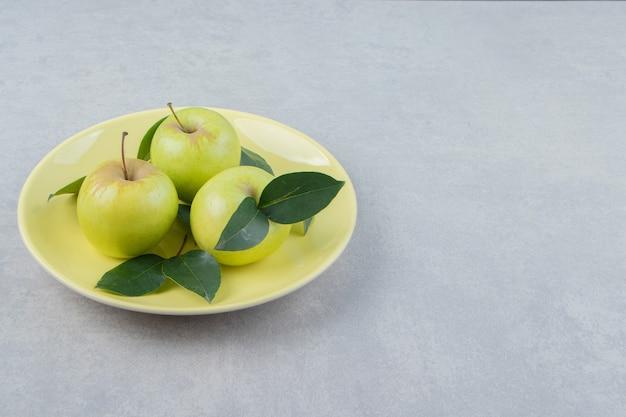 Mele mature fresche sul piatto giallo.