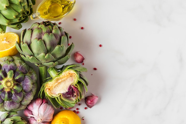 Fresh ripe artichokes, lemon and garlic with olive oil and pepper on white marble table.