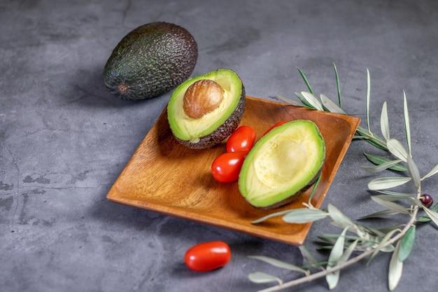 Свежий спелый авокадо и некоторые черри помидоры на деревянной тарелке, на темном фоне.