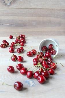 Куча свежих спелых ягод вишни на деревенском деревянном фоне вишня пролилась из белой миски