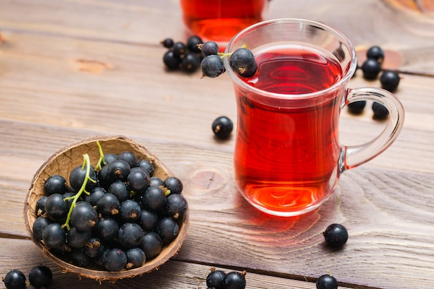 Fresh ripe black currant compote in a glass and a bowl of berries on a wooden table