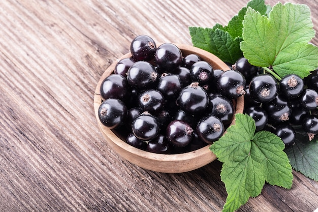 Fresh ripe black currant in wooden bowl with original leaves on rustic old background.