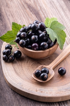 Fresh ripe black currant in wooden bowl with original leaves on rustic old background