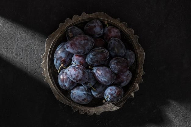 Свежие спелые голубые сливы в миске в луче света на черном фоне. творческий снимок. вид сверху