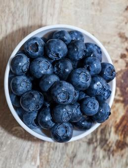 ガラスのボウルに入れられた新鮮な熟したブルーベリー白いプレートに入れられたブルーベリーブルーベリーは生で食べたりデザートを作ったりするのに使用できます