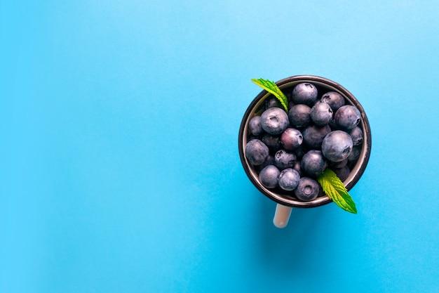 금속 머그잔에 민트와 신선한 익은 블루 베리 열매