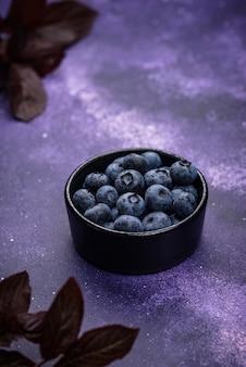 Свежая спелая черника в черной миске на фиолетовом фоне