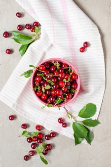 Fresh ripe cherries in the bowl on the textured grey table