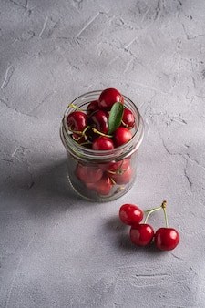 Fresh ripe cherry branch near to cherries with green leaves in glass jar