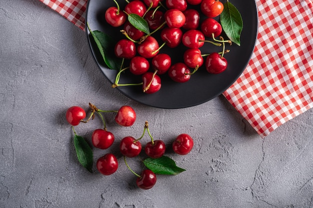 Fresh ripe cherry fruits with green leaves on black plate with red tablecloth