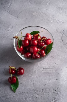 Fresh ripe cherry fruits with green leaves in glass bowl
