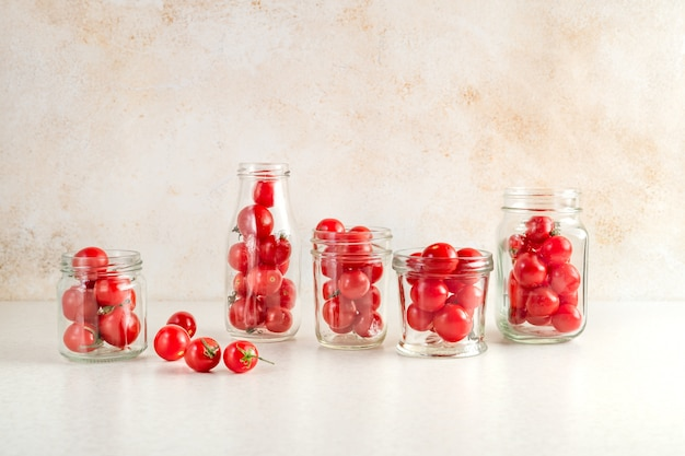 Fresh ripe cherry tomatoes in various glass jars on kitchen table prepared for preservation