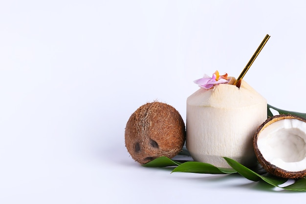 Fresh and ripe coconuts on white surface