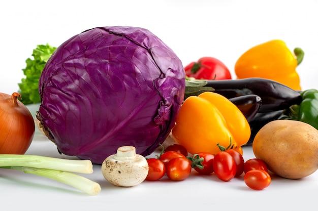 Свежие спелые цветные овощи на белом фоне