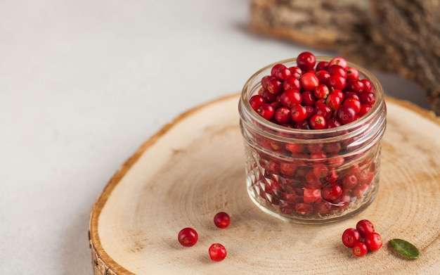Fresh ripe cranberries in a transparent glass jar on a wooden stand. autumn, useful berries. harvest..