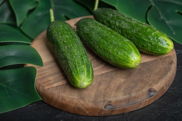 Fresh ripe cucumbers on wooden board.