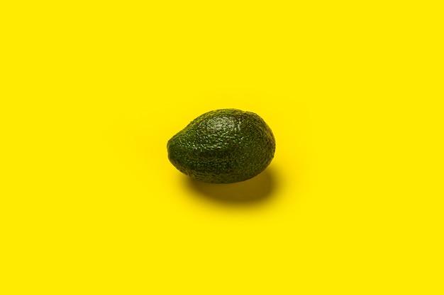 Свежие спелые темно-зеленые целые авокадо на желтом