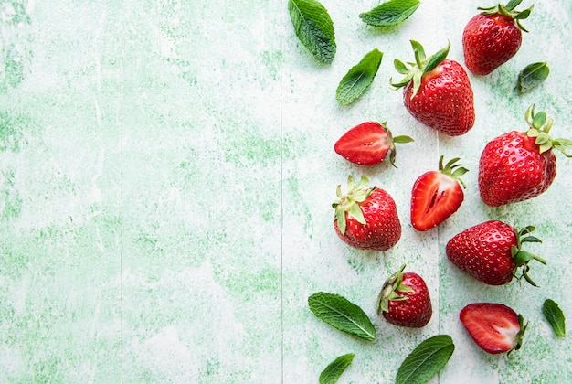 Fresh ripe delicious strawberries  on a green wooden background