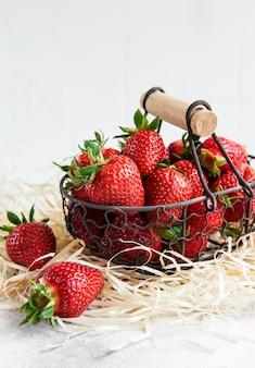 회색 돌 배경에 바구니에 신선한 익은 맛있는 딸기