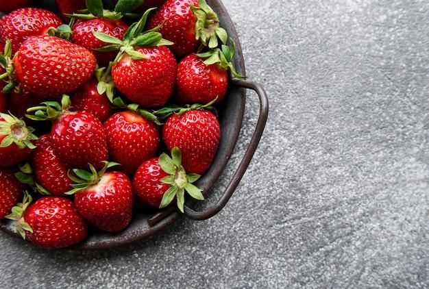회색 돌 배경에 있는 금속 그릇에 신선하게 익은 맛있는 딸기