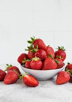 회색 돌 배경에 흰색 그릇에 신선한 익은 맛있는 딸기