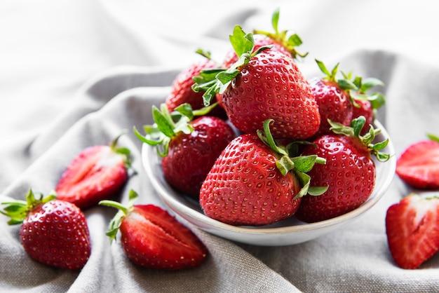 회색 직물 배경에 있는 흰색 그릇에 신선하게 익은 맛있는 딸기