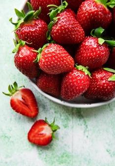 녹색 나무 배경에 있는 흰색 그릇에 신선하게 익은 맛있는 딸기
