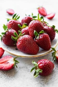 회색 돌 배경에 흰색 접시에 신선한 익은 맛있는 딸기