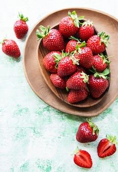 녹색 나무 배경에 있는 나무 그릇에 신선하게 익은 맛있는 딸기