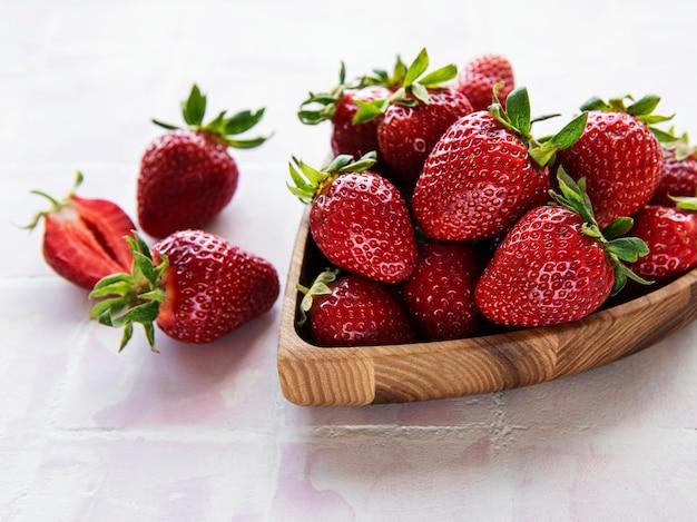 분홍색 타일 배경에 있는 나무 하트 모양의 그릇에 신선하게 익은 맛있는 딸기