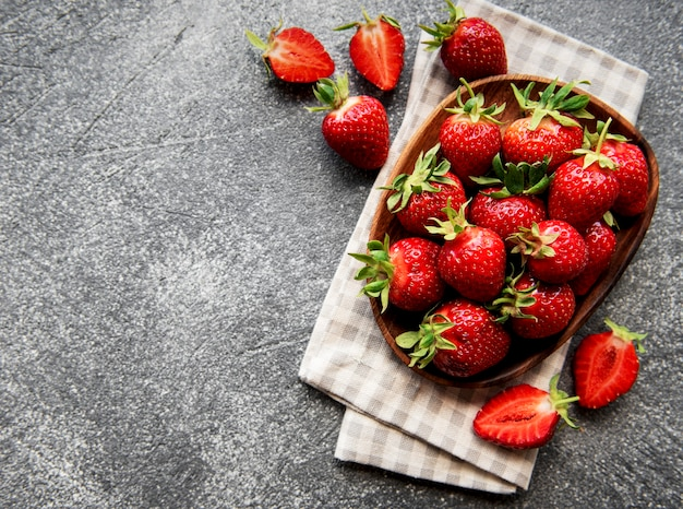 Fresh ripe delicious strawberries in a white bowl on a gray stone background