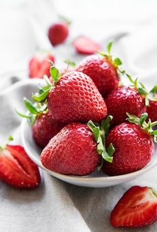 Fresh ripe delicious strawberries in a white bowl on a gray textile background