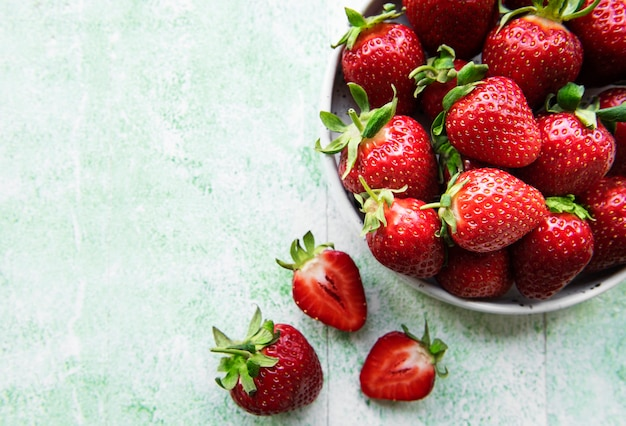 Fresh ripe delicious strawberries in a white bowl on a green wooden background