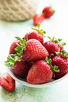 Fresh ripe delicious strawberries in a white bowl on a green wooden background Premium Photo