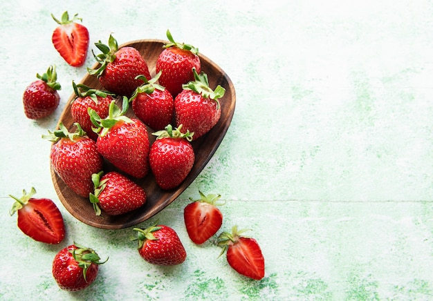Fresh ripe delicious strawberries in a wooden bowl on a green wooden background