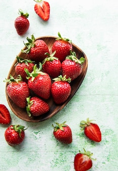 Fresh ripe delicious strawberries in a wooden bowl on a green wooden background Premium Photo
